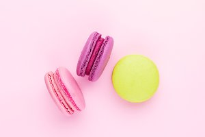 Three colorful macarons on pink.