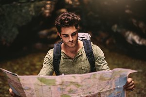 Male hiker using a map to locate