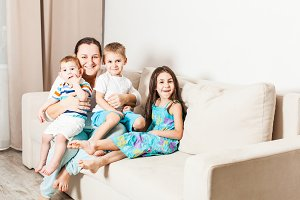 A woman with children are sitting on