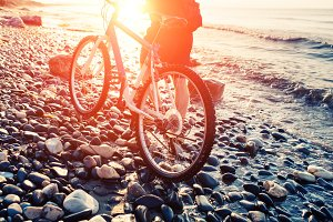 Man with bicycle on a sea shore