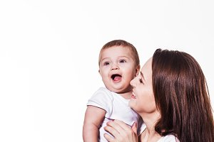 Small cute baby laughing in mother's