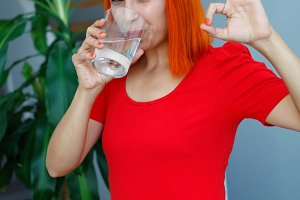 Happy woman drinking a glass of wate