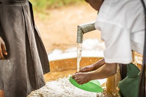 African boy cleans at water pump