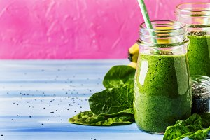 Green smoothies in glass bottles on