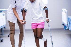 Female doctor assisting girl to walk