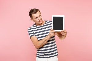 Portrait of young man holding tablet