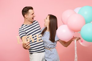 Portrait of couple hold wooden word