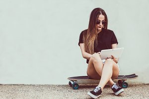Young woman sitting on skateboard an