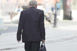 An old man in a black suit walks
