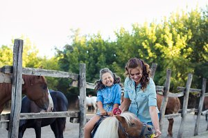 A small smiling girl on cute pony wi