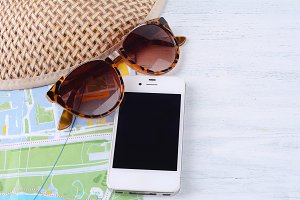 A map with sunglasses, a smartphone