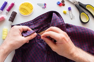man sews a button