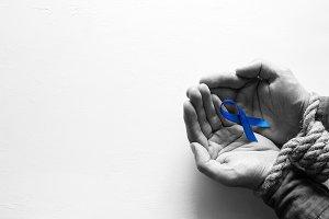 slave holds blue ribbon