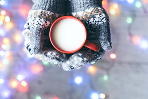 Hands in mittens holding cup of milk