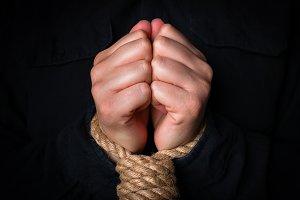 bound hands on a black background