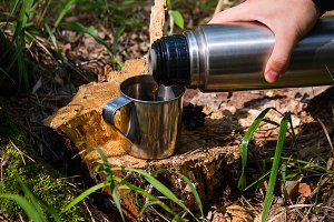traveler man pours tea from thermos