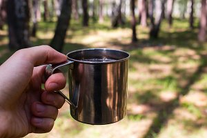 traveler holding a mug of tea