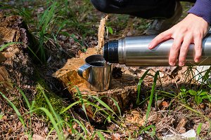 hiker pours tea from a thermos
