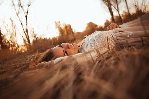 girl lying on the field on a sunset