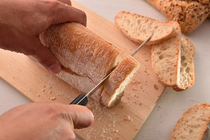 Chef slicing bread in slices top