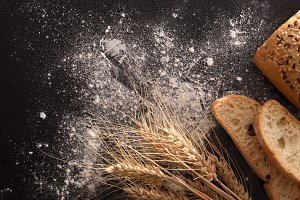 Bread wheat and flour on black table