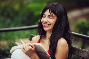 woman reading a book and laughing