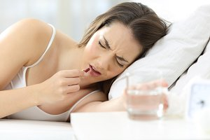 Ill woman taking pill lying on a bed