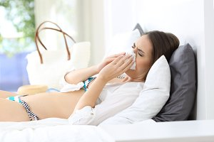 Ill woman sneezing in an hotel
