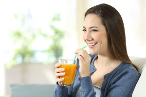 Happy girl holding an orange juice