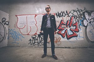 Hipster photographer man on grafitti