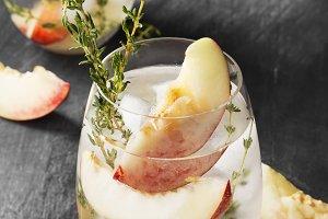Peach lemonade with thyme on a dark