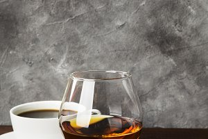 Glass of cognac and coffee in white