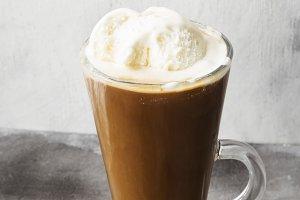 Ice coffee with ice cream on gray ba