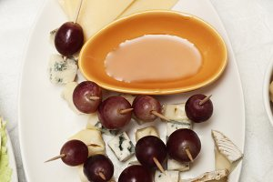 plate of cheese, grapes and honey on