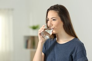 Woman drinking tap water in a glass