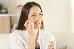 Woman applying moisturizer cream on