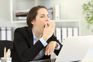 Tired executive yawning at office