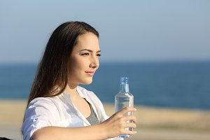Serious woman holding a water bottle