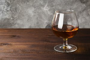 Cognac in glass on wooden background