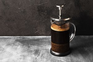 Coffee in french press on dark backg