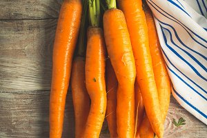 Raw carrots on rustic wooden backgro