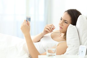 Worried woman taking a contraceptive