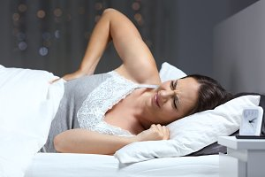 Woman suffering back ache on the bed