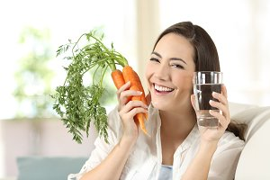 Woman showing healthy carrots