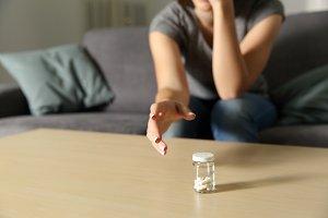 Woman hand reaching a bottle of pill
