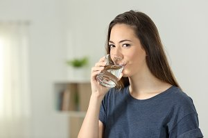 Woman drinking water looking at you