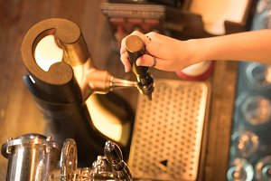 The bartender's hands pour beer from