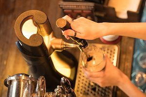 The barman's hands pour beer from