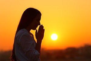 Backlight of a woman praying