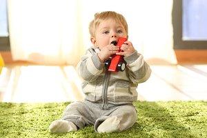 Baby sitting on a carpet biting